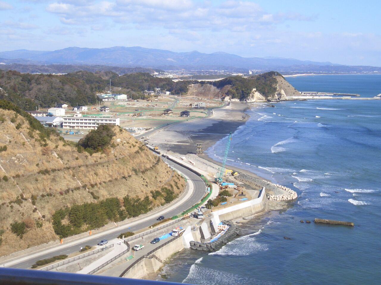 大津波にすっかりのみこまれた塩屋埼灯台直下の海岸線と復旧工事が始まったころの被災地
